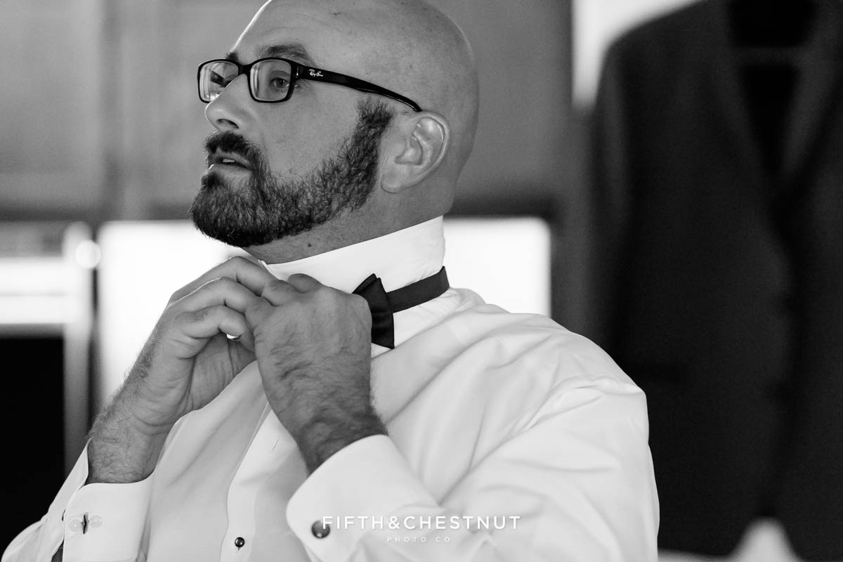 Groom putting tie on before his Bright fall wedding at the Grove by Reno Wedding Photographer