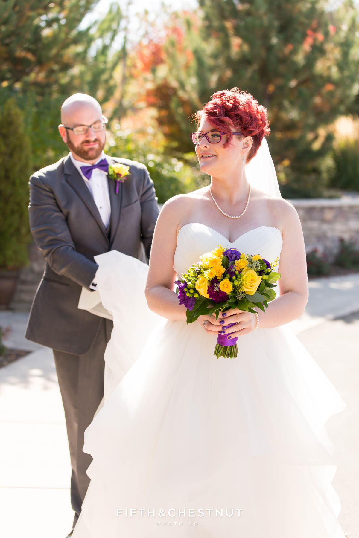 groom carries bride's train for a Bright fall wedding at the Grove by Reno Wedding Photographer