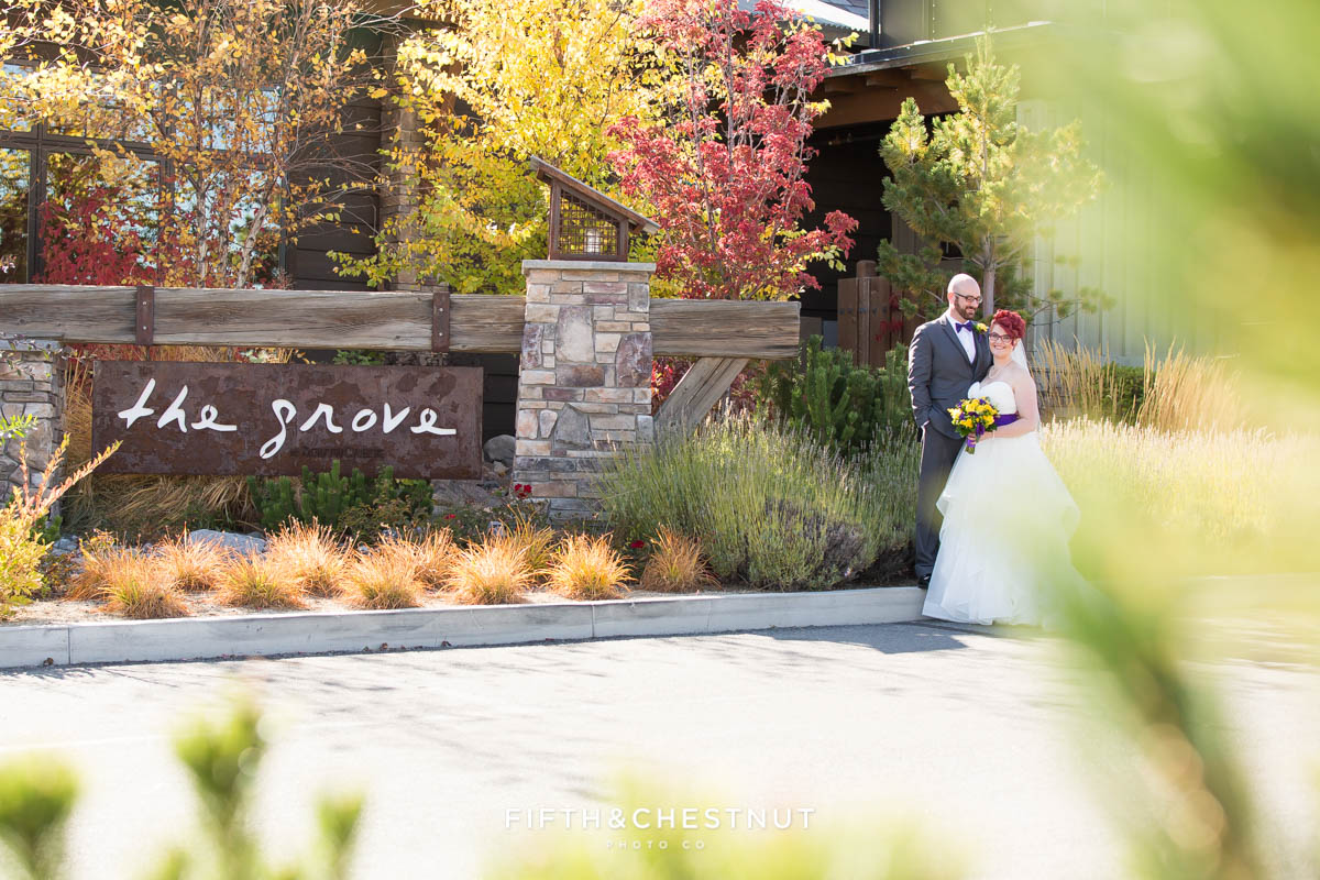 bride and groom stand in front of the grove for their bright fall wedding