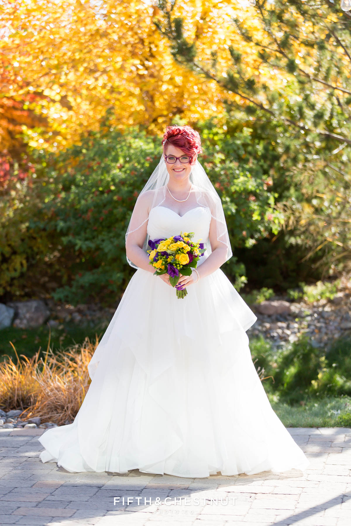 Portrait of bride in front of green and orange foliage for a Bright fall wedding at the Grove by Reno Wedding Photographer