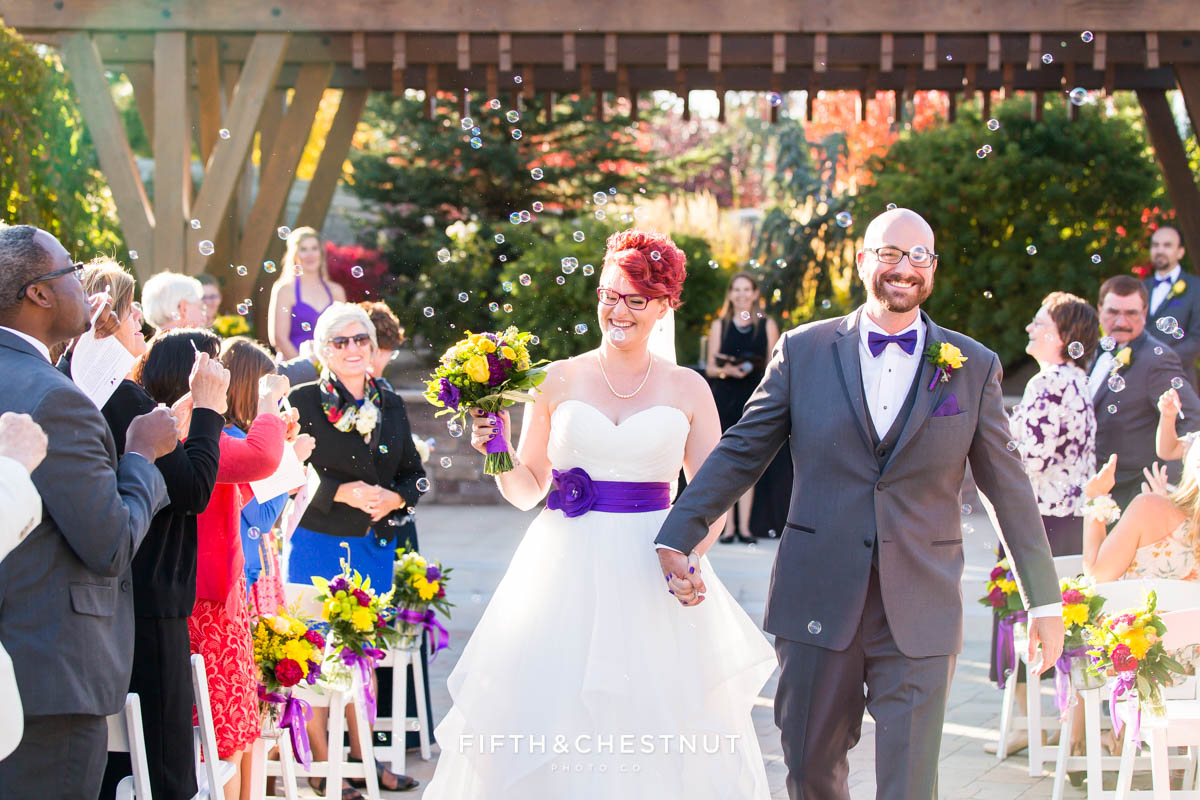 bride and groom walk down an aisle of bubbles at the end of their ceremony at The Grove
