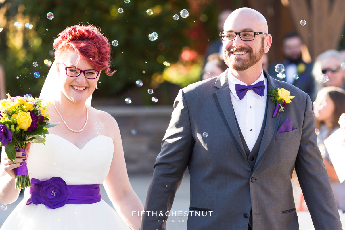 Bride and groom walk past bubbles after their ceremony for a Bright fall wedding at the Grove by Reno Wedding Photographer