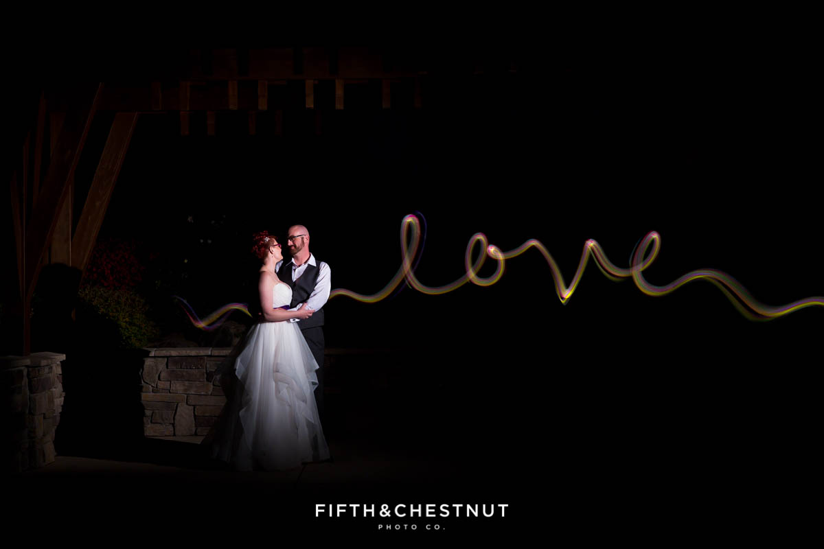 bride and groom are lit up as the word LOVE is created next to them from using glow sticks and long exposure for a Bright fall wedding at the Grove by Reno Wedding Photographer