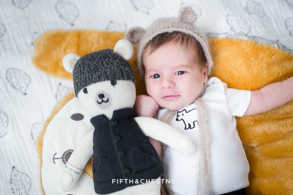 Baby boy wearing bear hat with Cuddle & Kind bear laying on fox blanket