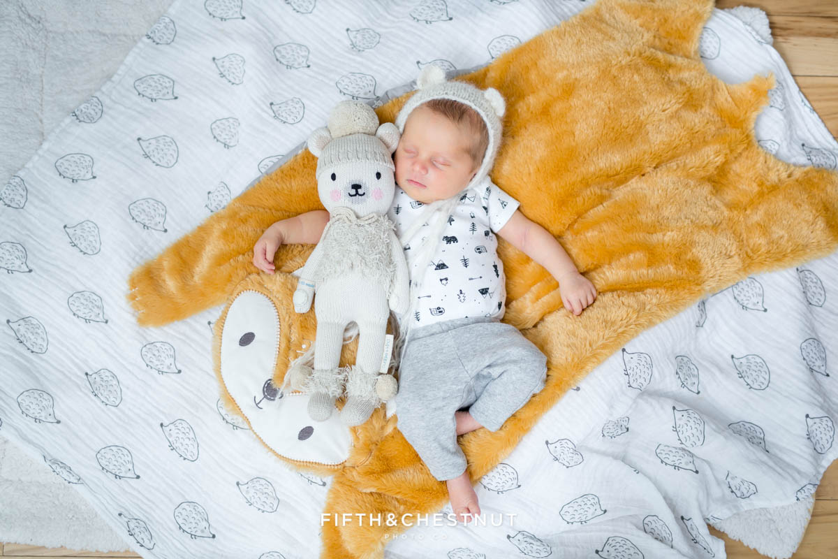 Baby girl wearing bear hat by Lavender Gray on a fox blanket with a Cuddle & Kind bear