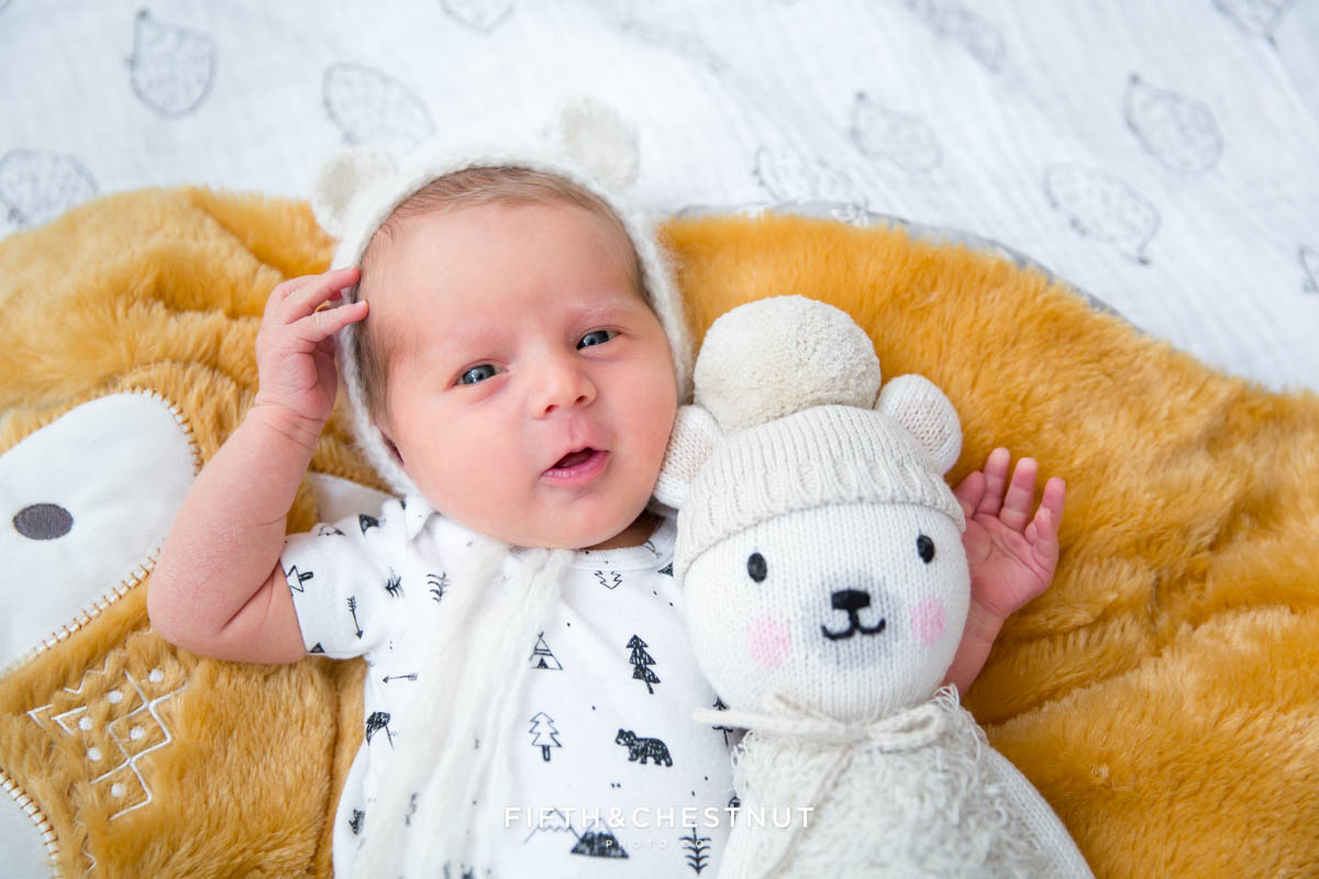 Baby girl wearing bear hat by Lavender Gray on a fox blanket with a Cuddle & Kind bear for a professional portrait by Reno Baby Photography