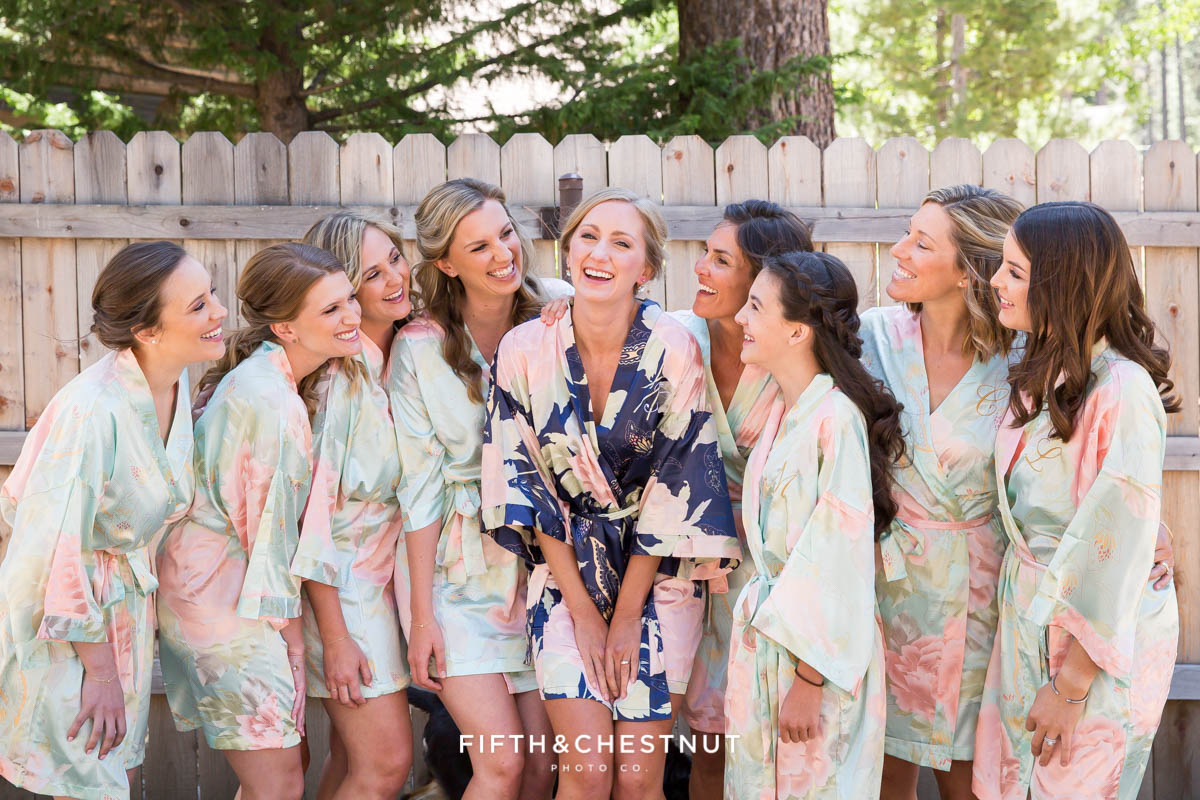 bride and bridesmaids in custom floral satin robes before getting dressed for a zephyr cove wedding by lake tahoe wedding photographer