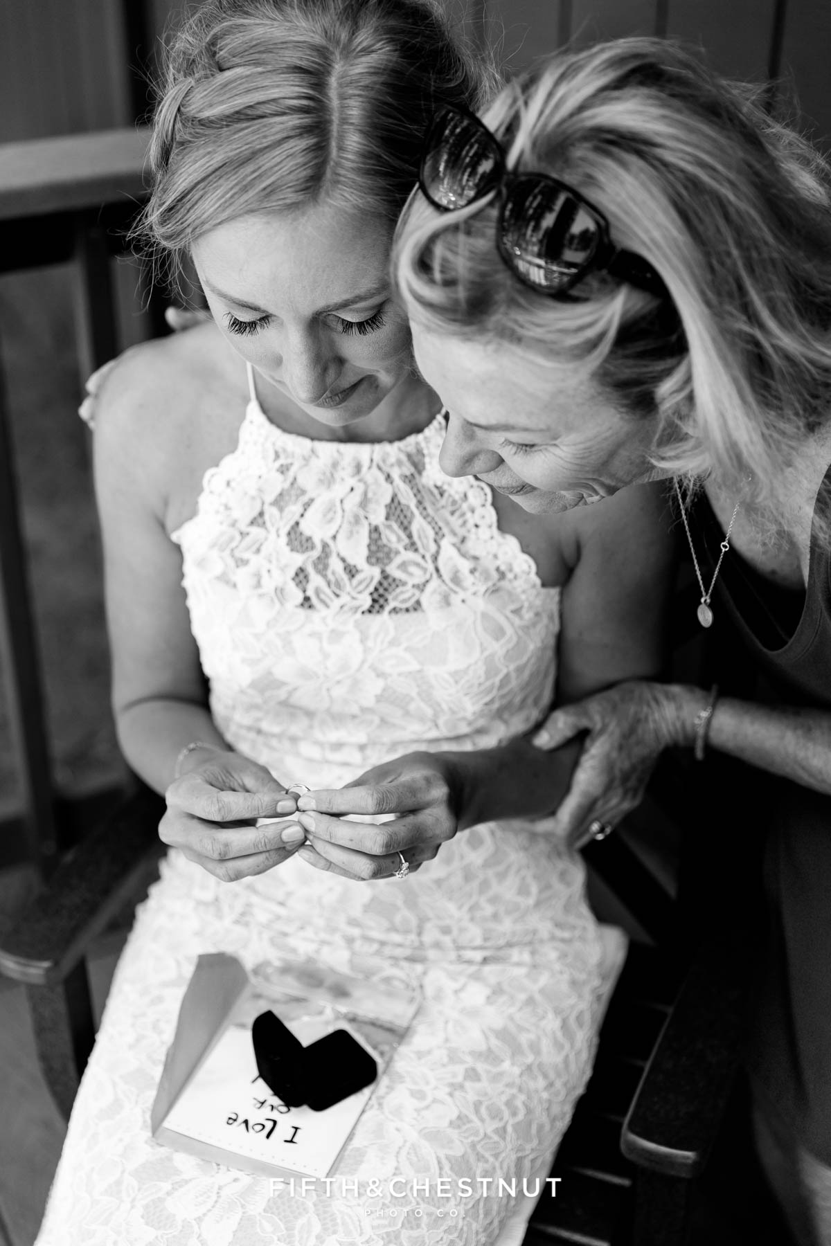 bride cries with her mom after opening a gift from her groom