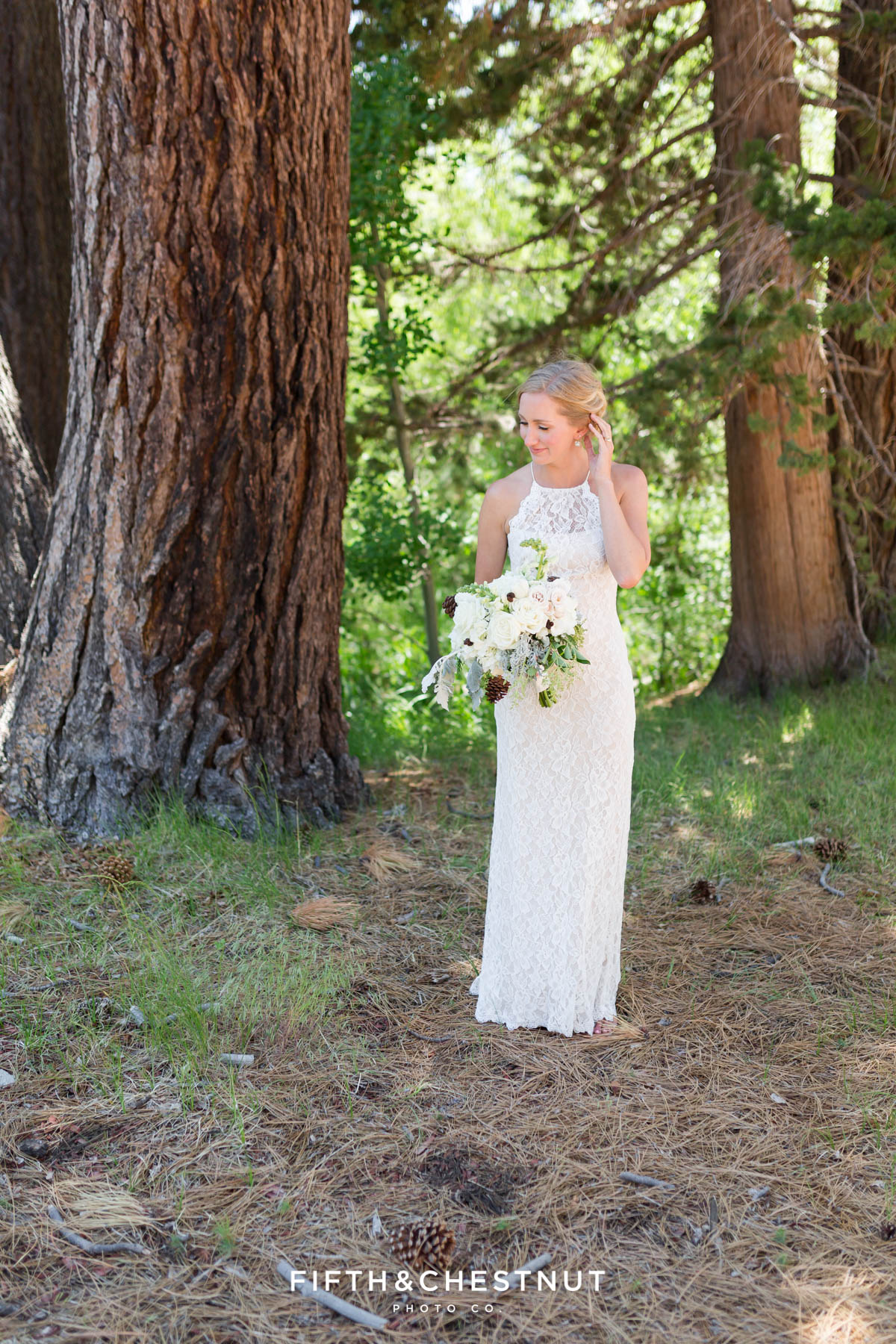 bride fixes hair in the forest before her zephyr cove wedding by lake tahoe wedding photographer