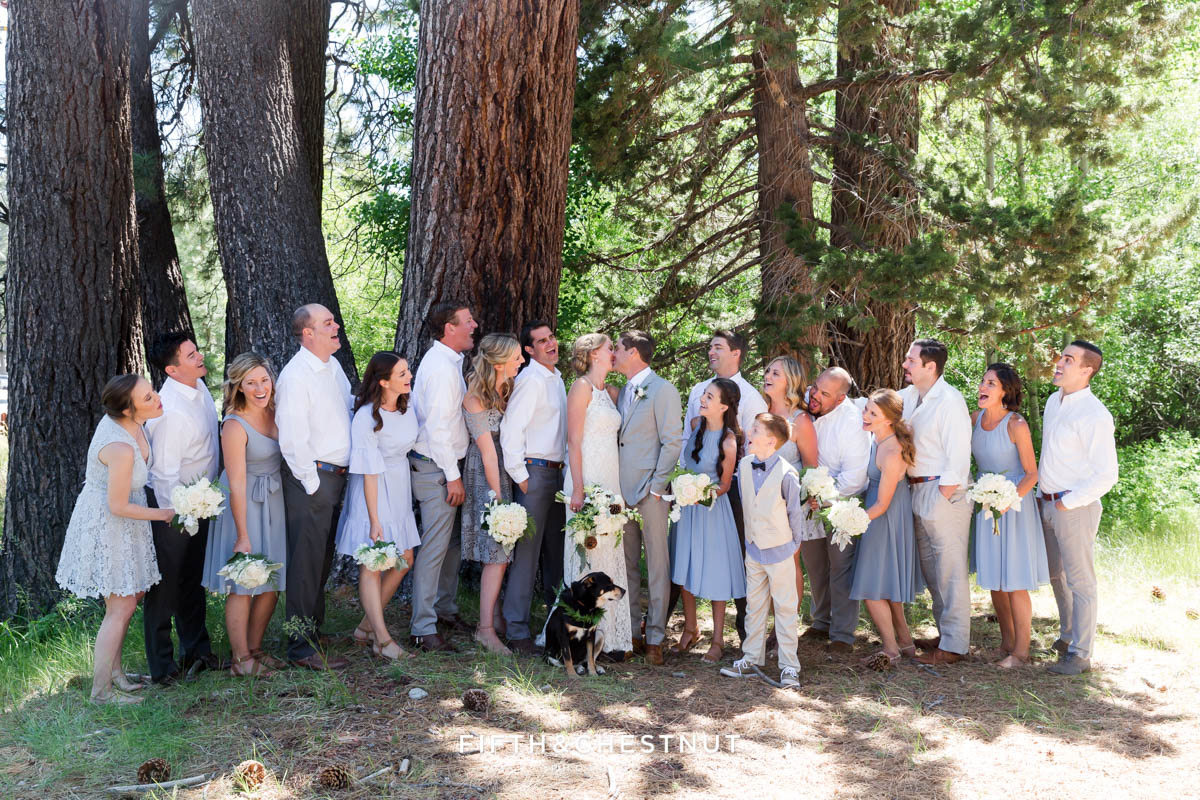 bride and groom kiss while heckled by wedding party for their zephyr cove wedding in south lake tahoe