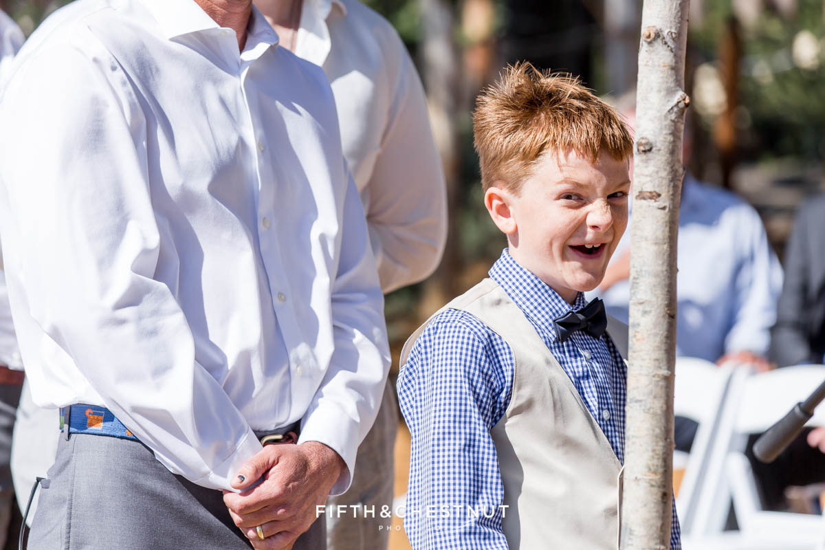 ring bearer spots the camera at a wedding ceremony in lake tahoe