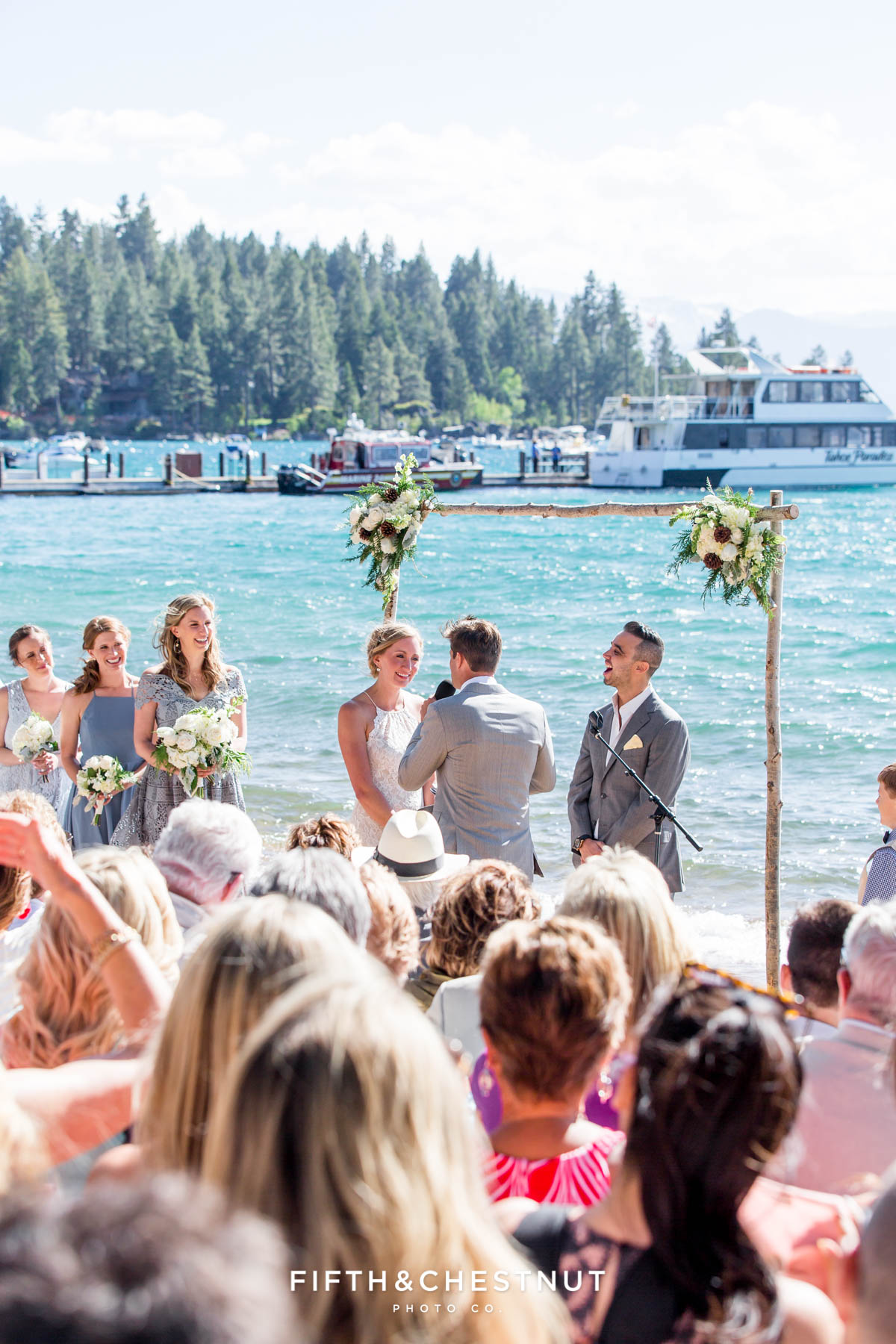 everyone laughs during a lake tahoe wedding ceremony with boats in the background