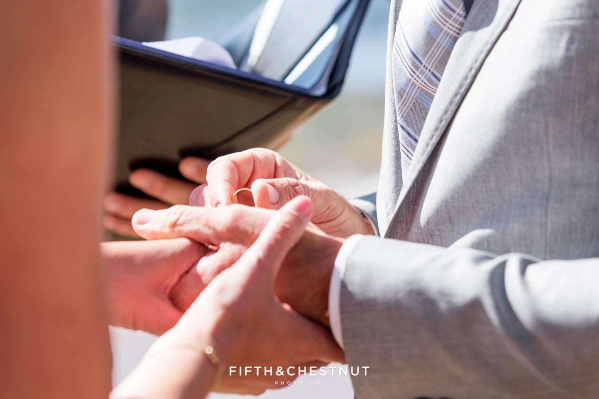 groom puts wedding band on his bride at a lake tahoe wedding