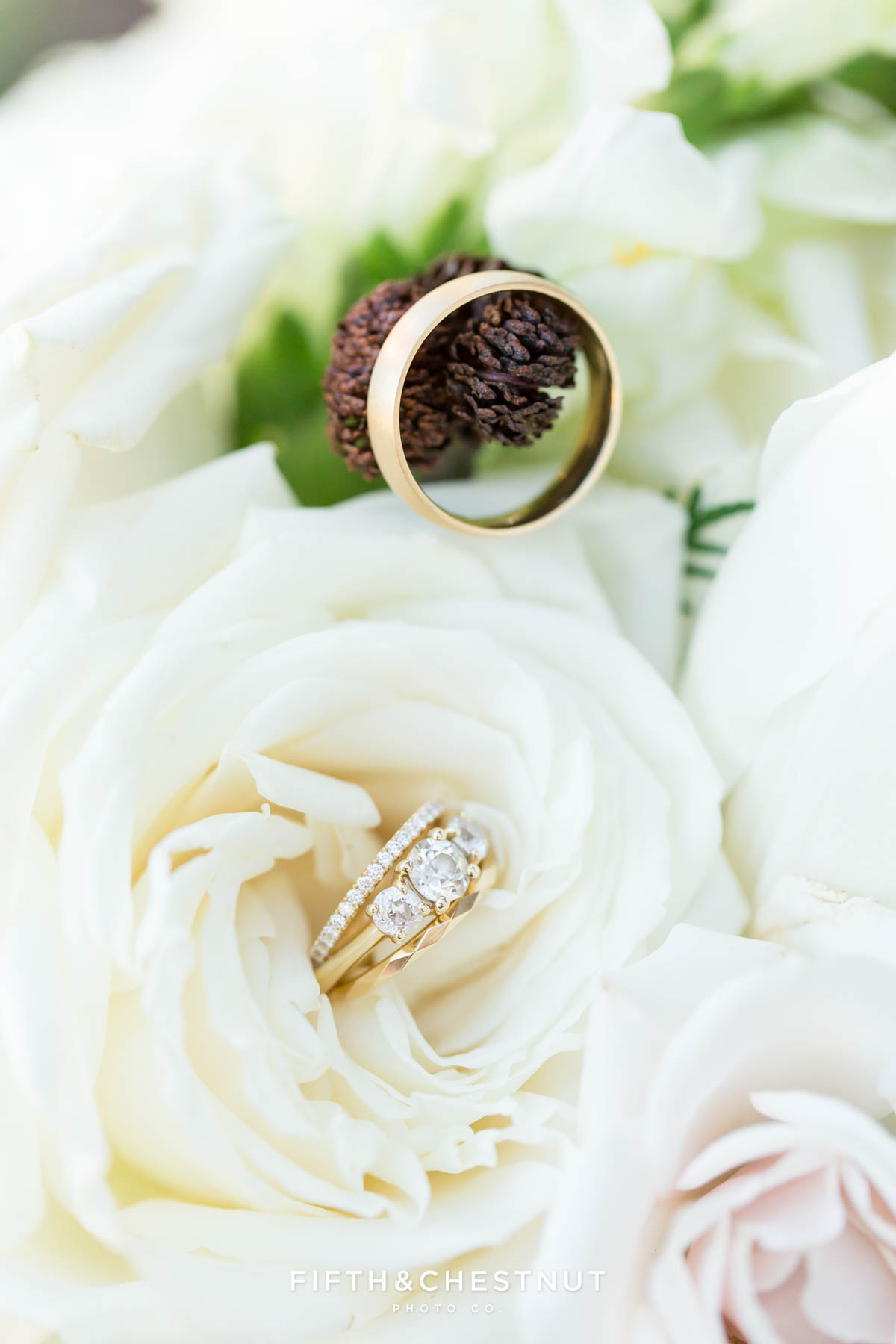 wedding rings on flowers and tiny pine cones by lake tahoe wedding photographer