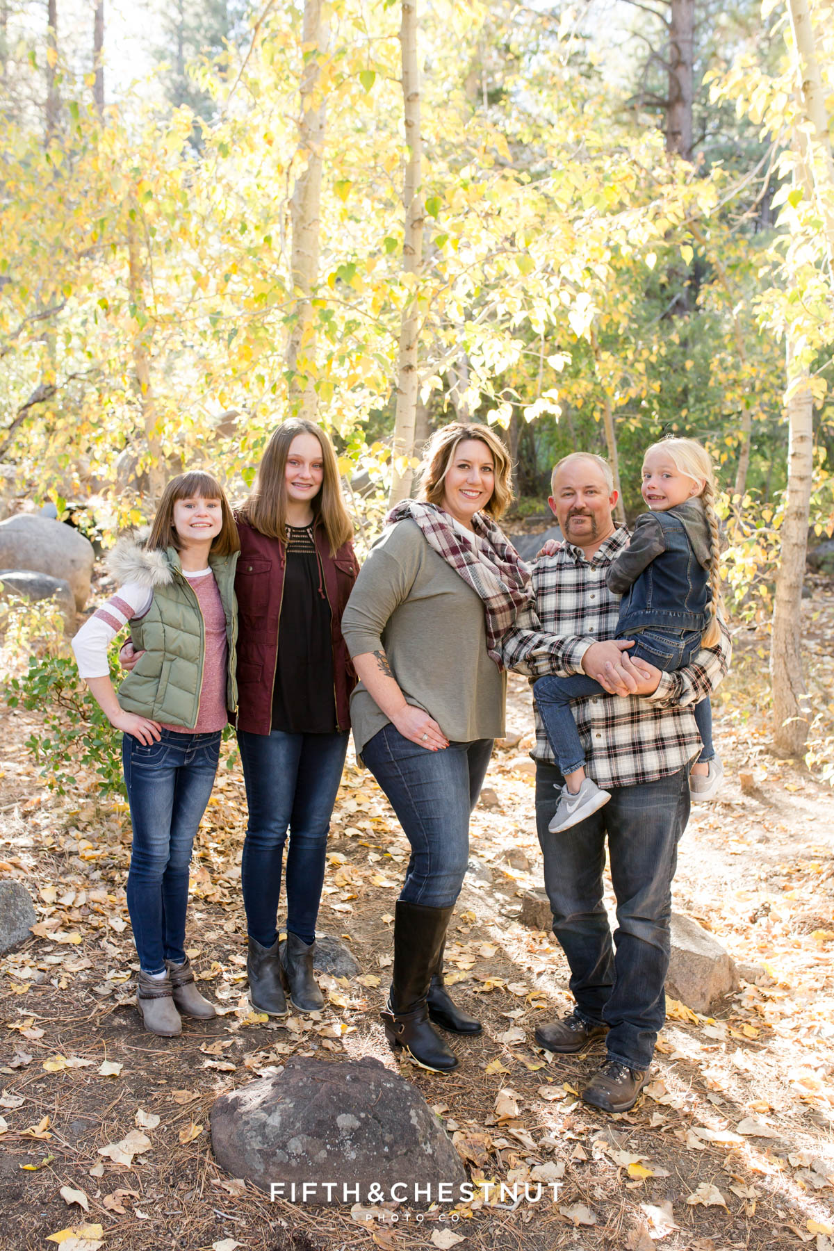 Family stands in front of aspen trees together for Galena Creek Reno fall portraits