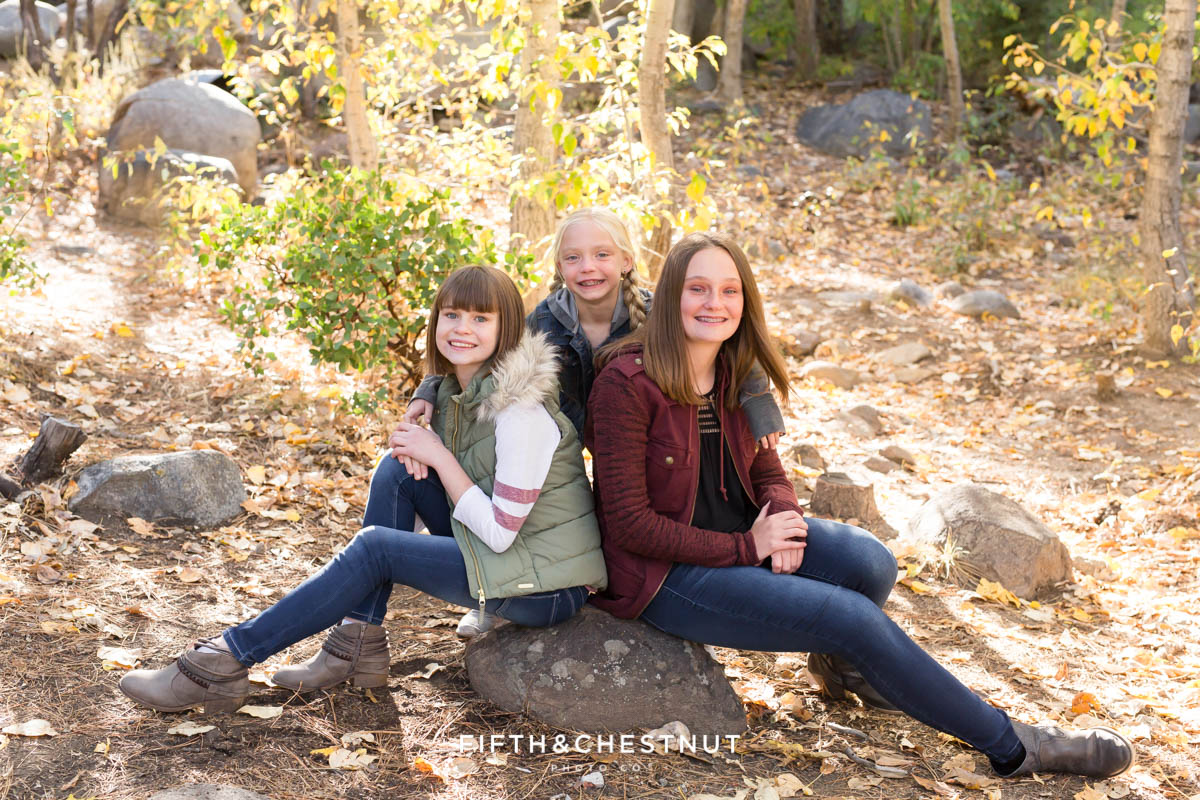 sisters sit on a rock together for Galena Creek Reno fall portraits