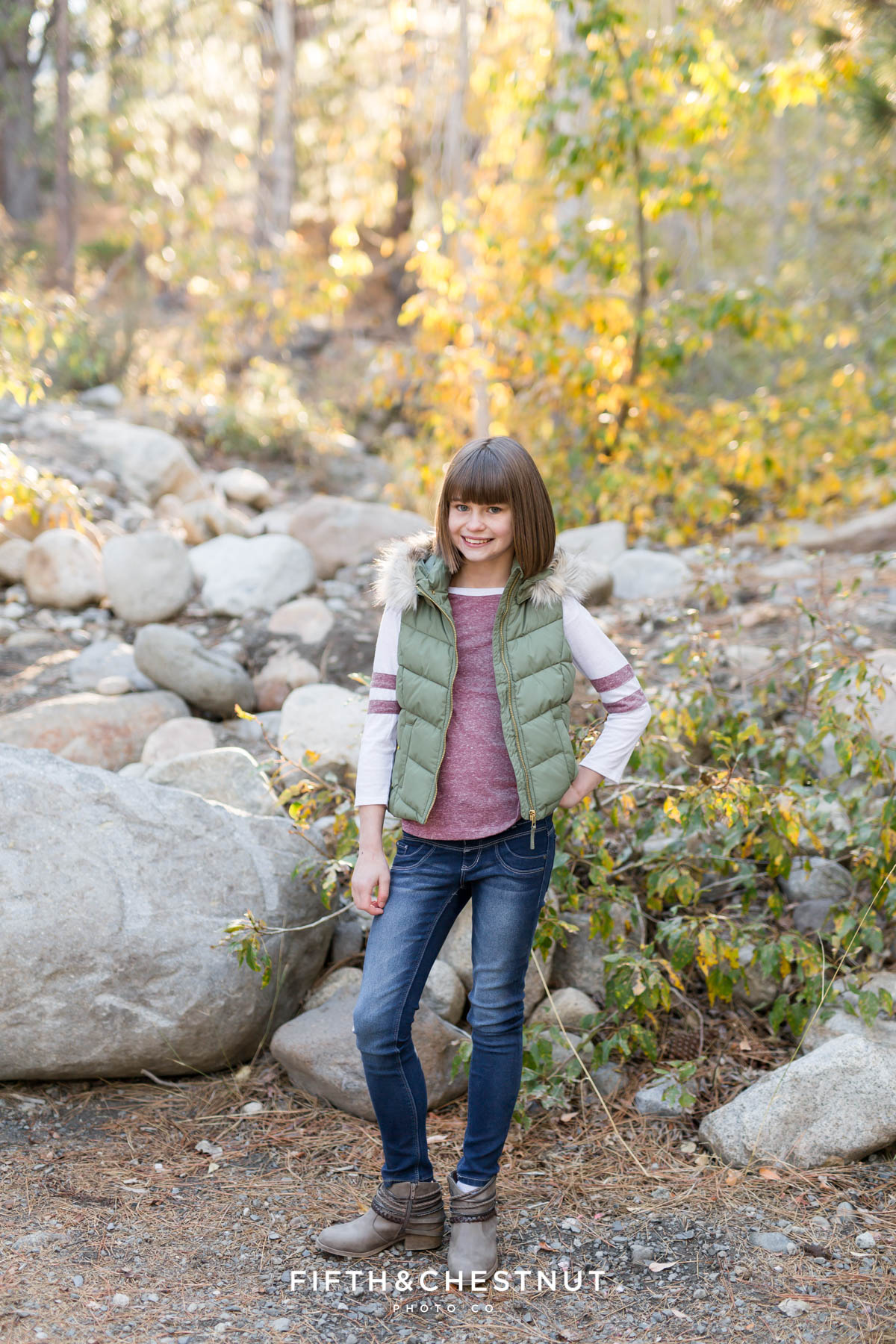 teenage girl in green puffy vest poses in front of rocks for Galena Creek Reno fall portraits by Reno Family Photographer