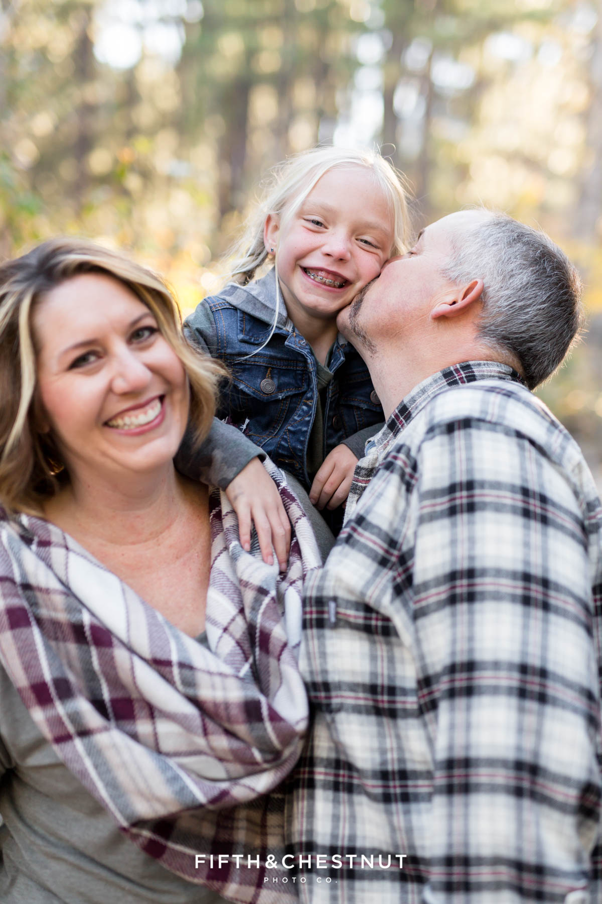 dad kisses daughter on cheek while mom laughs during Galena Creek Reno fall portraits by Reno Family Photographer