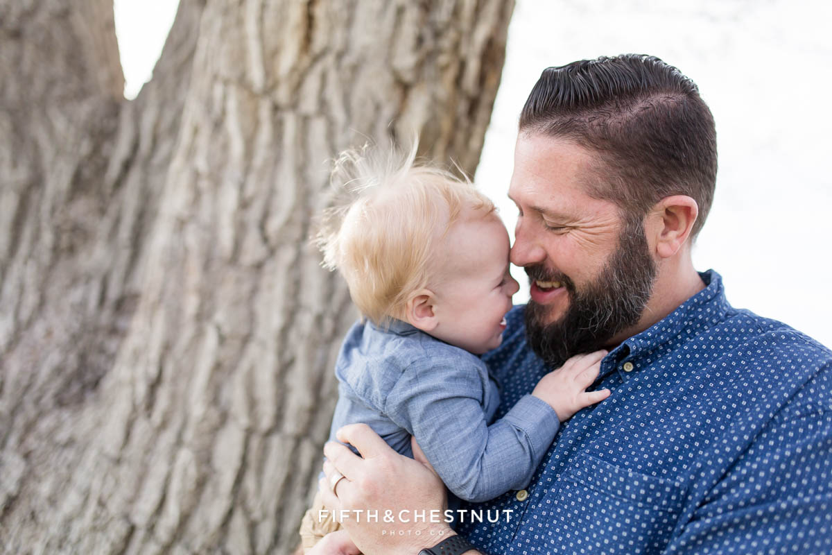 baby boy snuggling with dad for Golf Themed One Year Photos by Reno Baby Photographer