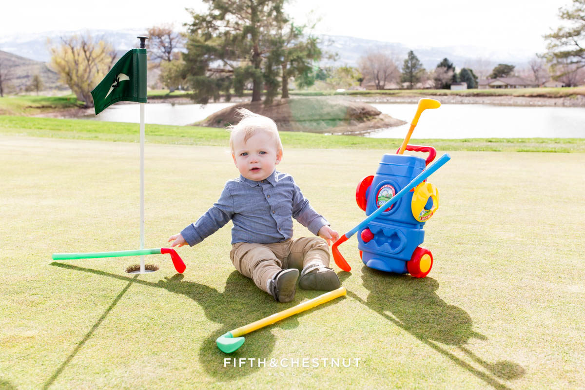 Finely dressed baby boy playing with toy golf clubs on the green for his Golf Themed One Year Photos by Reno Baby Photographer