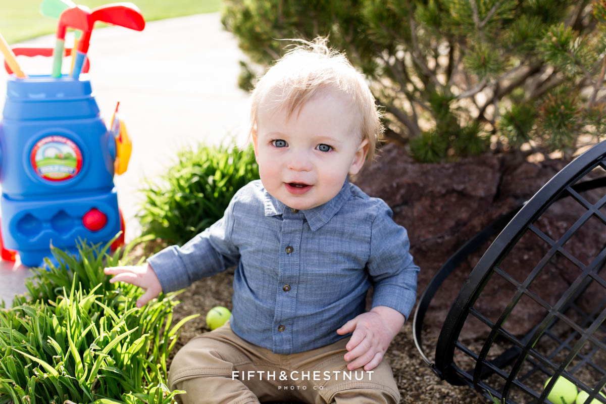 Baby boy posing and smiling with toy golf clubs and a basket of golf balls at Hidden Valley Country Club for his Golf Themed One Year Photos by Reno Baby Photographer