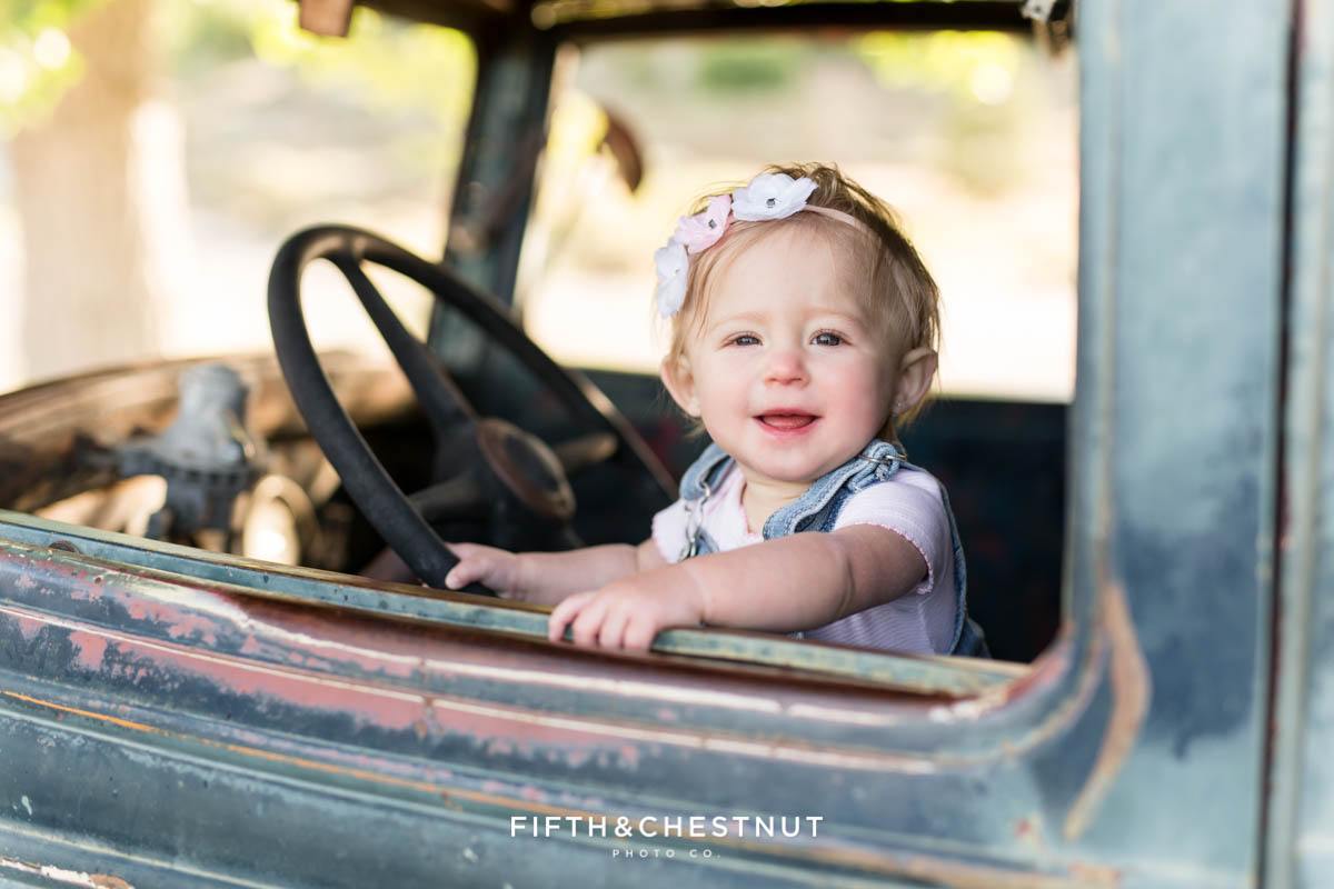 One Year old girl pretending to drive a vintage truck for her Rustic Spring Baby Girl One Year Portraits at Bartley Ranch by Reno Baby Photographer
