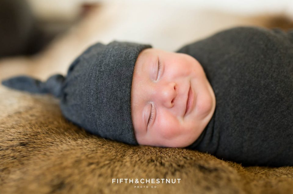 A smile caught on camera during a newborn photoshoot of a baby boy in a gray cap and gray swaddle on an elk skin pelt during his reno newborn photo session