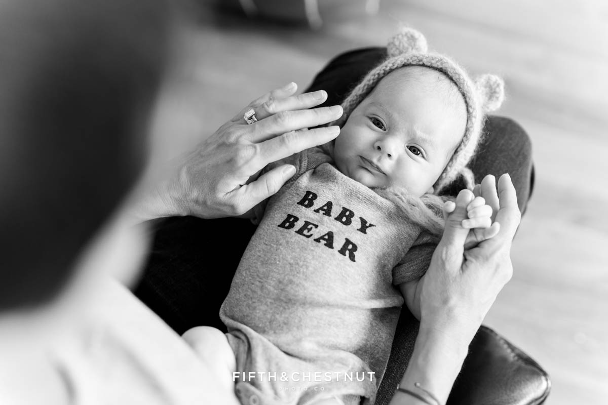 "black and white image of a newborn baby boy wearing a ""baby bear"" onesie and a bear hat for lifestyle newborn photos by Reno Newborn Photographer"