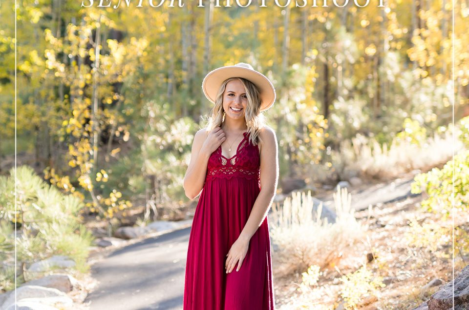 Reno high school senior girl in red dress with wide brimmed hat walking down a paved path lined with yellow aspen trees in the fall at galena creek park for reno senior photos by Fifth and Chestnut Photo Co.