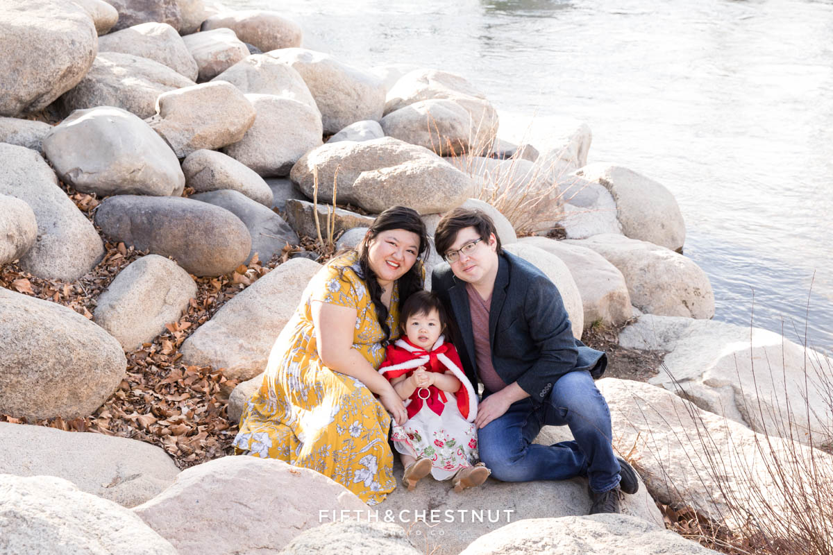 Family of three poses on rocks by the truckee river for Reno 2 year portraits of their little girl