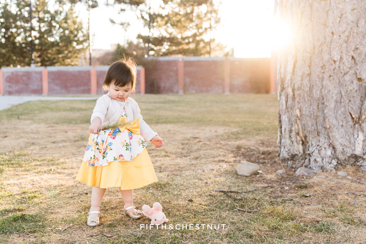 sweet Reno 2 year portraits of a little girl playing with pine needles in the park while wearing a yellow floral dress