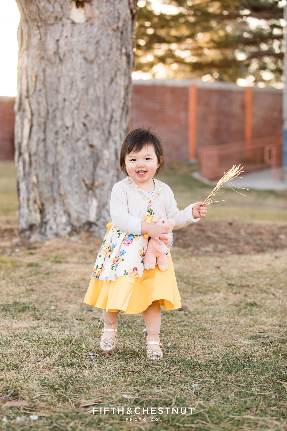 happy girl plays in a park for her Reno 2 year portraits in downtown reno