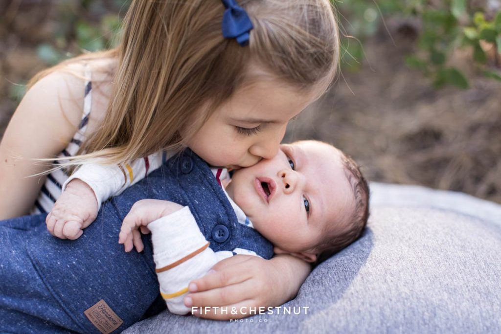 A big sister kisses her newborn baby brother on his cheek during his spring outdoor newborn portraits by Reno Newborn Photographer