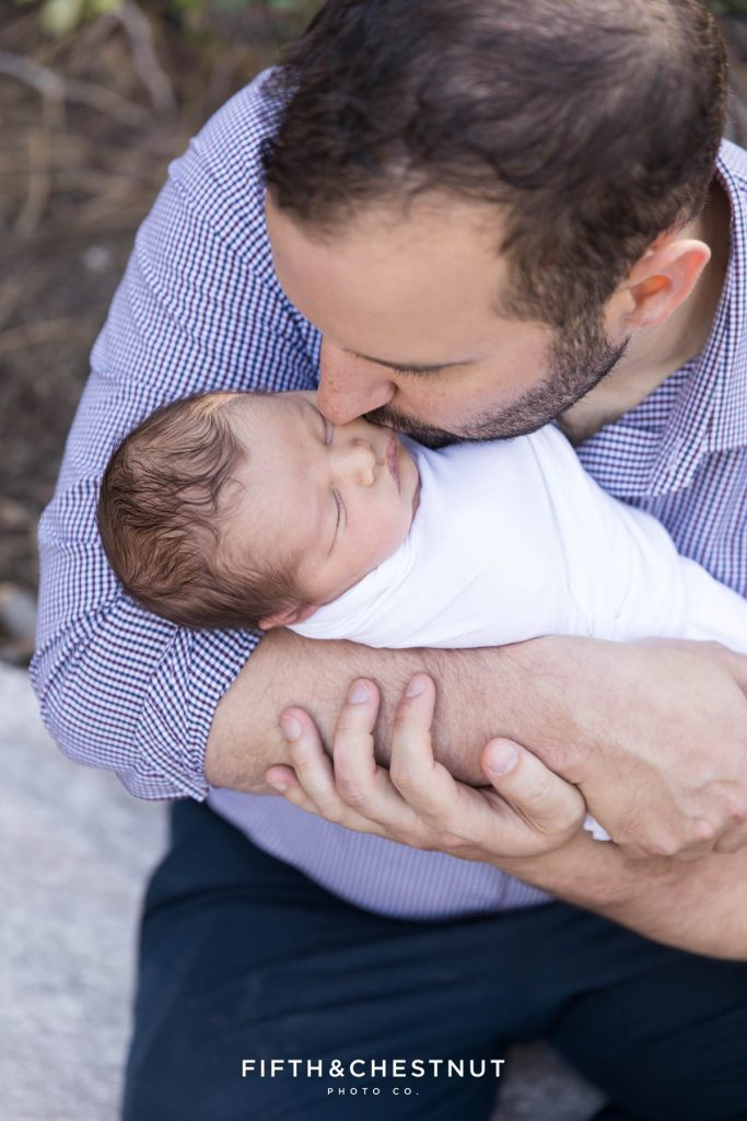A dad gently kisses his newborn baby on the cheek in the forest