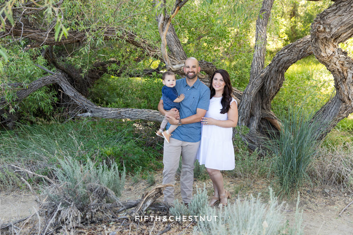 A young family of three stands in front of a beautiful tree at Evan's Canyon trail wearing blue, tan and white for their Happy Spring Family Photos by Reno Family Photographer