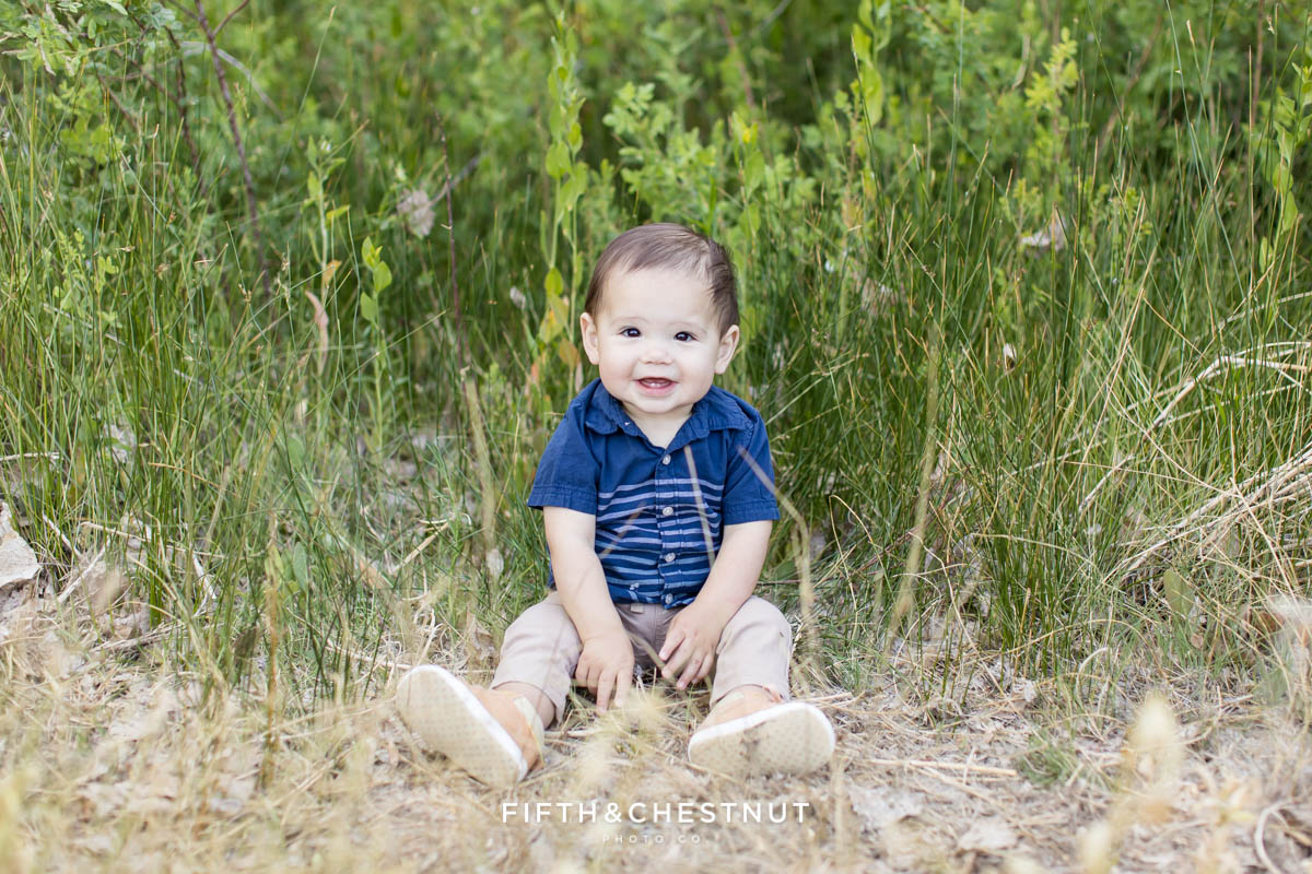 A portrait of a very happy one year old boy showing off his two bottom teeth during his happy spring family photoshoot