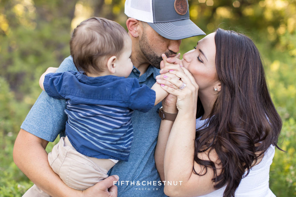 Parents kiss their one year old boy's hands for their Happy Spring Family Photos