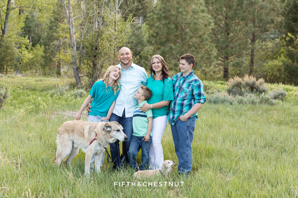 a family of five and their two dogs laugh together in a meadow for their Colorful Reno Family Portraits at Crystal Peak Park