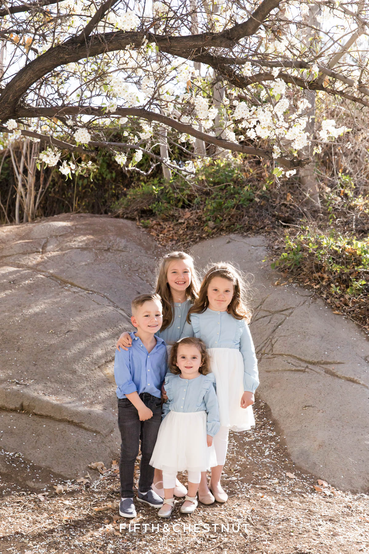 four children in pastel and neutral clothing huddle together for bright and airy family portraits at rancho san rafael