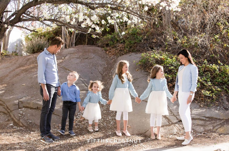 a family of six wearing neutral and pastel colors holds hands and smiles for their bright and airy family portraits