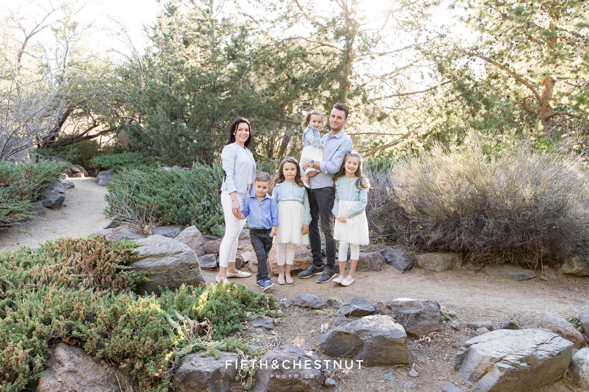 A sweet family of six stands together wearing pastel clothing for their bright and airy family portraits with Reno Family Photographer on a spring day