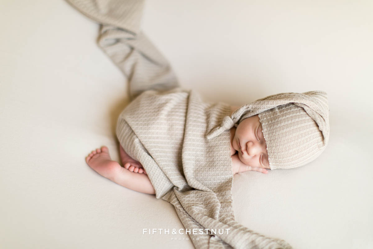 A soft waffle texture blanket covers a baby boy for his neutral newborn twin photos by Reno Family Photographer