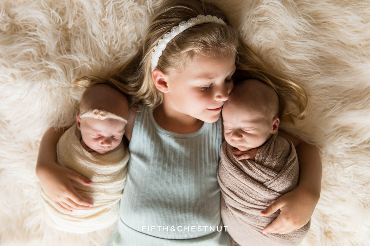 A big sister cuddles her baby twin siblings for their newborn twin photos by Reno Newborn Photographer