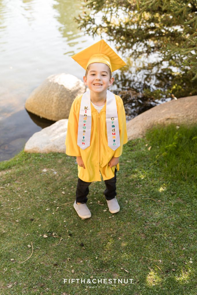 """Kindergarten Cap and Gown Portraits of a young boy wearing a gold gown, gold cap and a white sash that says """"kindergarten graduate"""" at UNR in the Spring by Reno Child Photographer"""