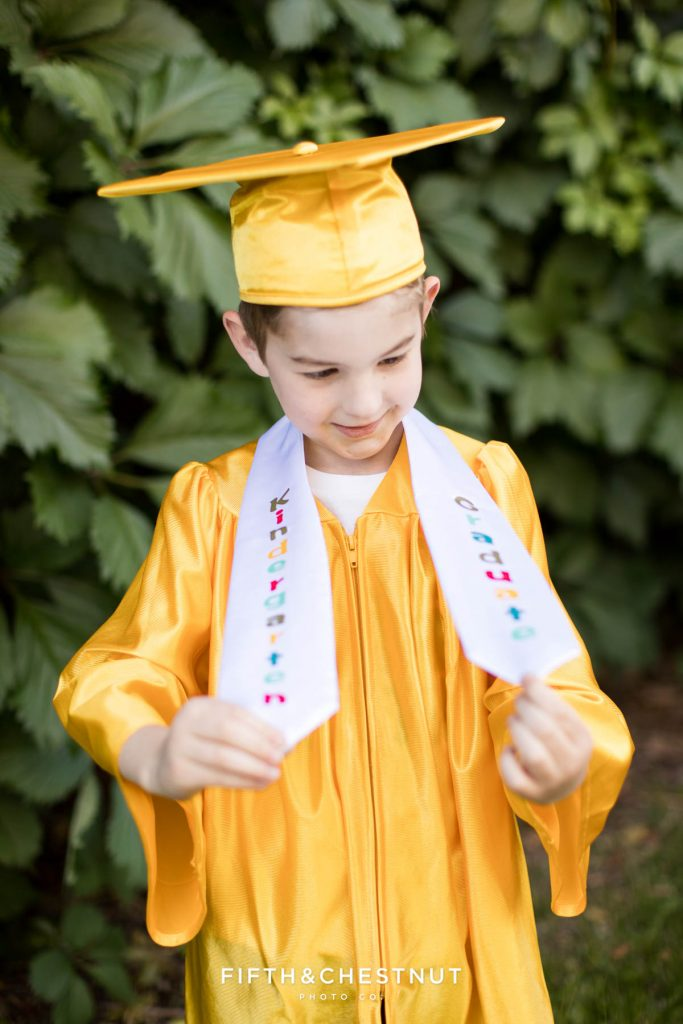 """Kindergarten Cap and Gown Portraits of a young boy wearing a gold gown, gold cap and a white sash that says """"kindergarten graduate"""" in front of an ivy wall at UNR in late spring"""