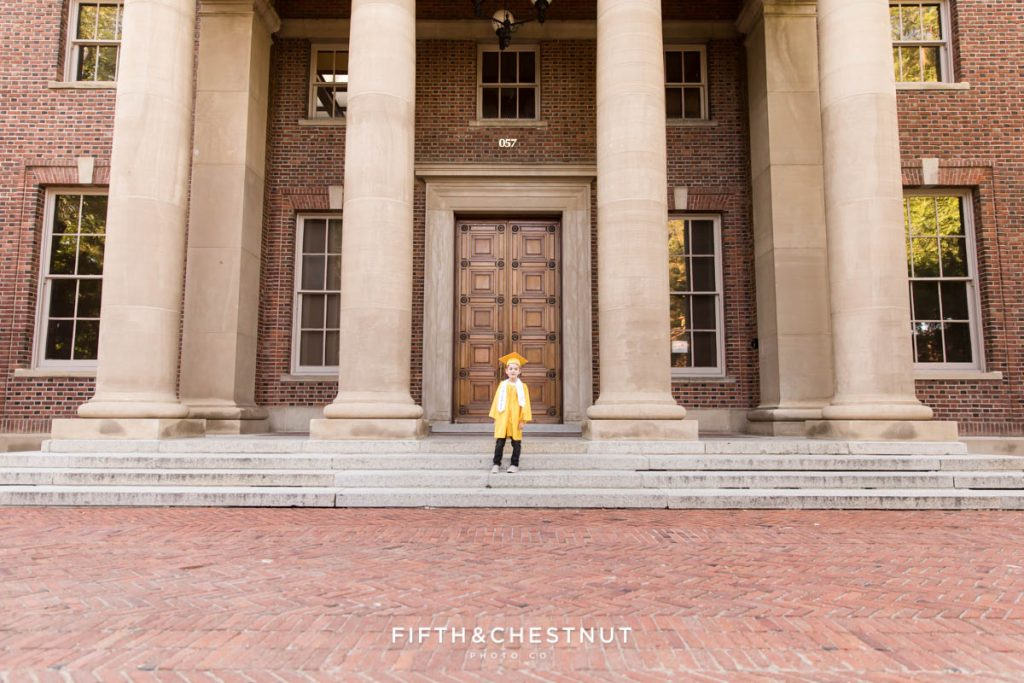 """Kindergarten Cap and Gown Portraits of a young boy wearing a gold gown, gold cap and a white sash that says """"kindergarten graduate"""" at UNR standing on the steps to an old building in the Spring by Reno Child Photographer"""