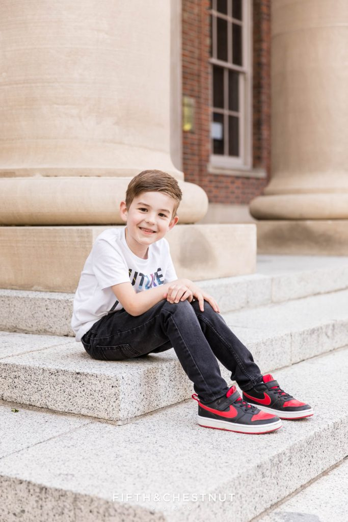 A young boy sits on steps to an old building at UNR for his kindergarten graduate pictures