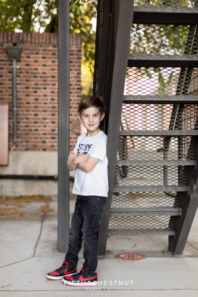 A young boy crosses his arms for his 6 year portraits at UNR by Reno Child Photographer