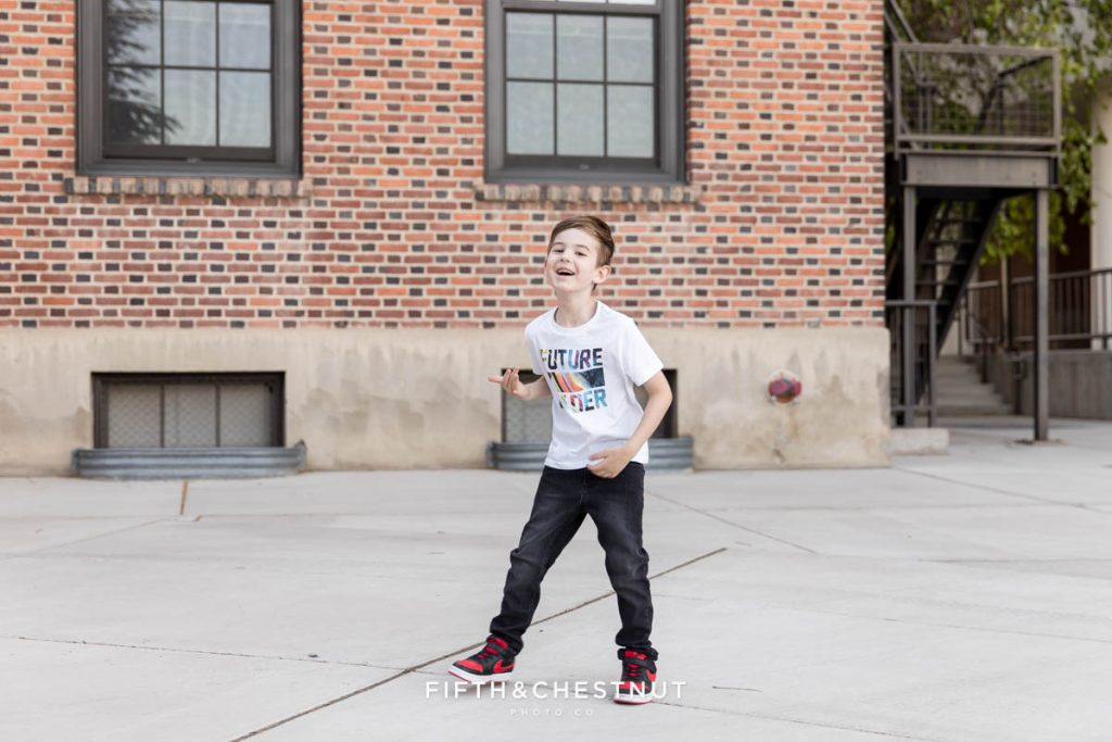 A young boy jumping in front of a brick building at UNR for his Reno child Portraits