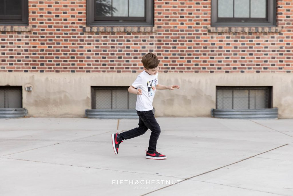 A young boy running wildly in front of a brick building at UNR for his Reno child Portraits